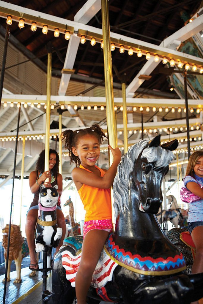 Children and adults alike enjoy a ride on a merry-go-round.